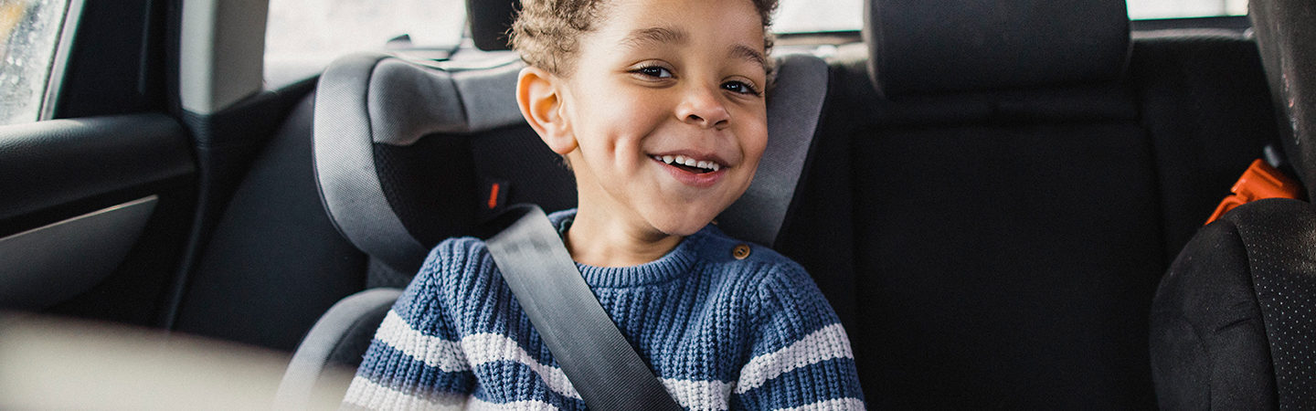 Little boy sitting in back seat of car