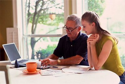 Father and daughter researching financial options online